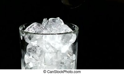 A cube of ice falling into a glass of water. close up. slow motion