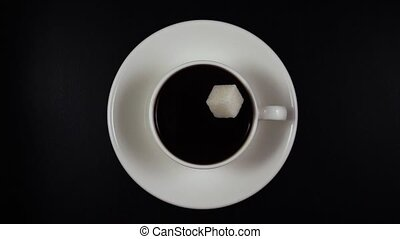 A cube of sugar falls into the coffee in a cup. Slow mo, top view