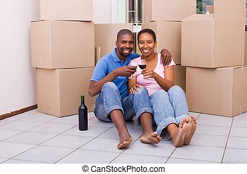 cuddling african couple - a cuddling african couple drinking...