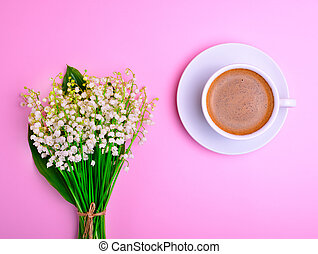 black coffee and a blooming bouquet of lilies of the valley o