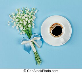 a Cup of black coffee on a saucer and a bouquet flowers lily of the valley on a blue background closeup, top view flat lay