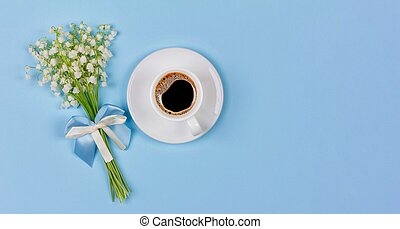 a Cup of black coffee on a saucer and a bouquet flowers lily of the valley on a blue background with copy space, top view flat lay