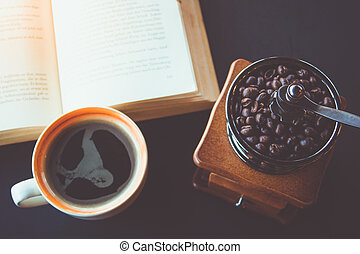 A cup of black coffee with book on table