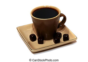 A cup of black coffee with chocolate candies