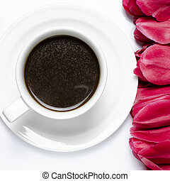 A cup of black coffee with red tulips on a white background