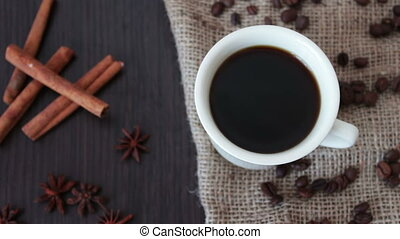 A cup of fragrant coffee on a wooden table. - A cup of black...