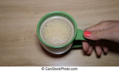 A cup of cappuccino in female hands - A cup of warm...