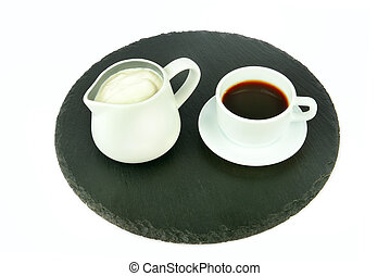 A cup of coffee and a jug of cream on a slate tray isolated on a white .