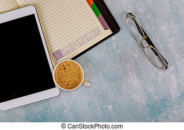 A cup of coffee and an open notebook on the table on notebook using a digital tablet with glasses the view top.
