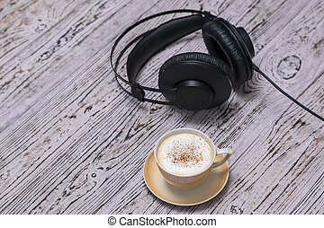 A Cup of coffee and black headphones with a wire on a wooden table.