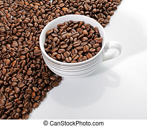 A cup of coffee beans on the edge o