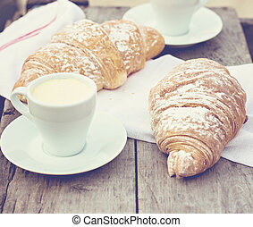 """A cup of coffee """"espresso"""" and croissant."""