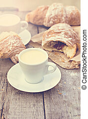 """A cup of coffee """"espresso"""" and croissant on the wooden table."""