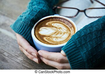 A cup of coffee hold by hand with book