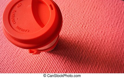 A cup of coffee is placed on an orange yoga mat.