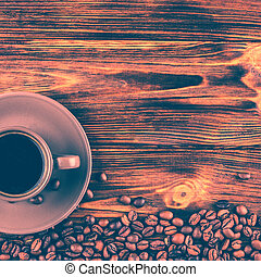 A cup of coffee on a wooden background with space for your text