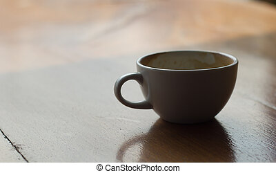 A cup of coffee on poor lighting in coffee shop.