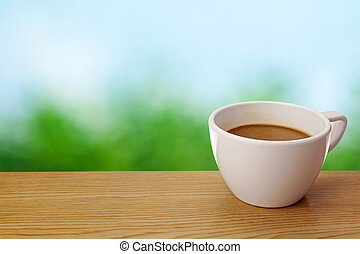 A cup of coffee on table over green background