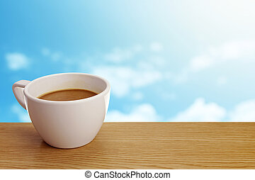 A cup of coffee on table over sky background