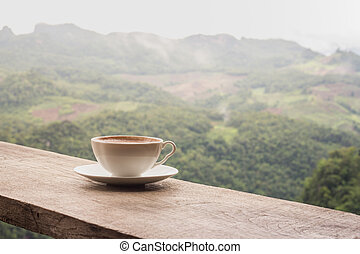 A cup of coffee on the table and a beautiful mountain background.