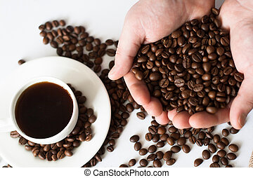 A cup of coffee on the table and coffee beans