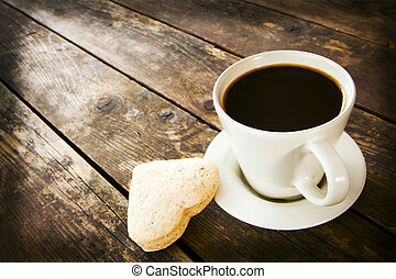A cup of coffee on the wooden board with heart-shaped cake.
