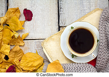 A cup of coffee on wooden table with fallen leaves.