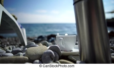 A cup of coffee with blue sea. White Cup on the rocks on the shore