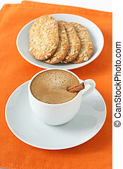 a cup of coffee with cookies