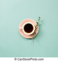 A cup of coffee with eucalyptus leaf on green background. top view, copy space