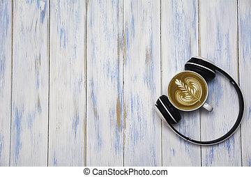 A cup of coffee with headphone on wooden table. Top view of coffee latte art with copy space. Drink and art concept.