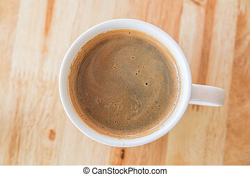 A cup of coffee with in a white cup on wooden background