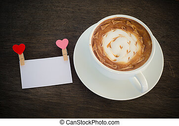 A cup of coffee with latte art and on wooden background