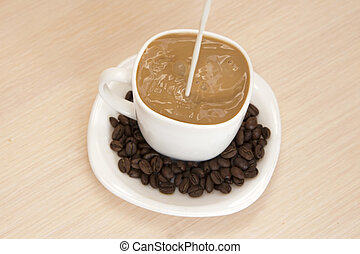 A cup of coffee with milk on a wooden background