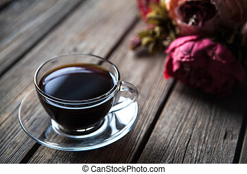 A cup of coffee with peonies on a wooden background. flowers