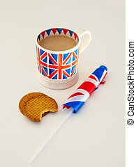 a cup of English tea and biscuits with a flag