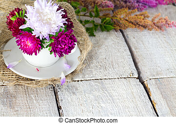 A cup of flower for decoration interior room. Pink beautiful flower on white table background.