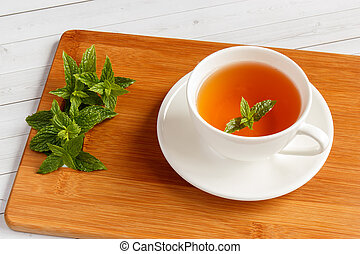 a cup of fresh mint tea on a wooden table with leaves of fresh mint, shallow depth of field and selective focus