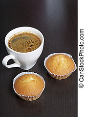 A cup of freshly brewed coffee and muffins. On a dark background.