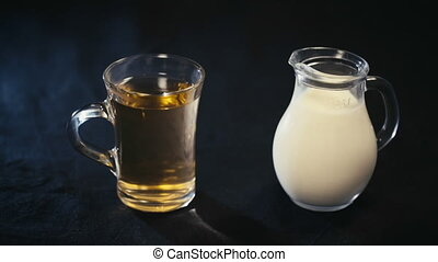 a Cup of green tea and a jug of milk