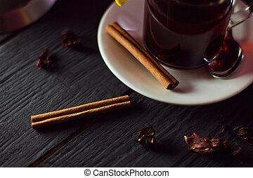 A Cup of hibiscus tea from Sudanese rose with cinnamon sticks on old wooden background black