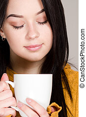 A cup of hot beverage. - Beautiful winter brunette holding a...