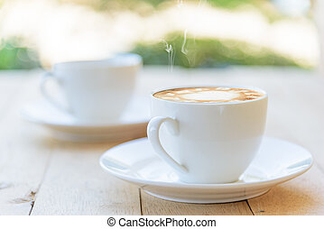 a cup of hot coffee on the wood table
