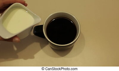 A cup of hot coffee with milk on the white table in slow motion