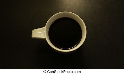 A cup of hot coffee with steam on the black table
