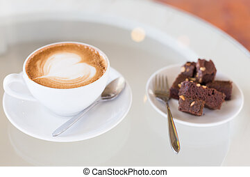 A cup of hot Latte coffee on old wooden table with brownie cake