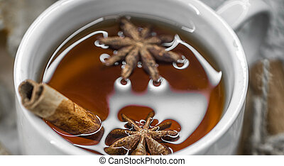 Cup of hot tea with cinnamon sticks and spices