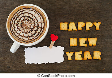 """A cup of latte art and alphabet """"happy new year"""" made from bread"""