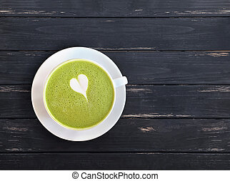 A cup of matcha latte drink with drawn small heart on the black wooden table