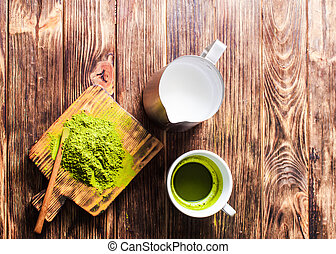 A cup of Matcha tea with milk jug and powdered green tea on wooden table.